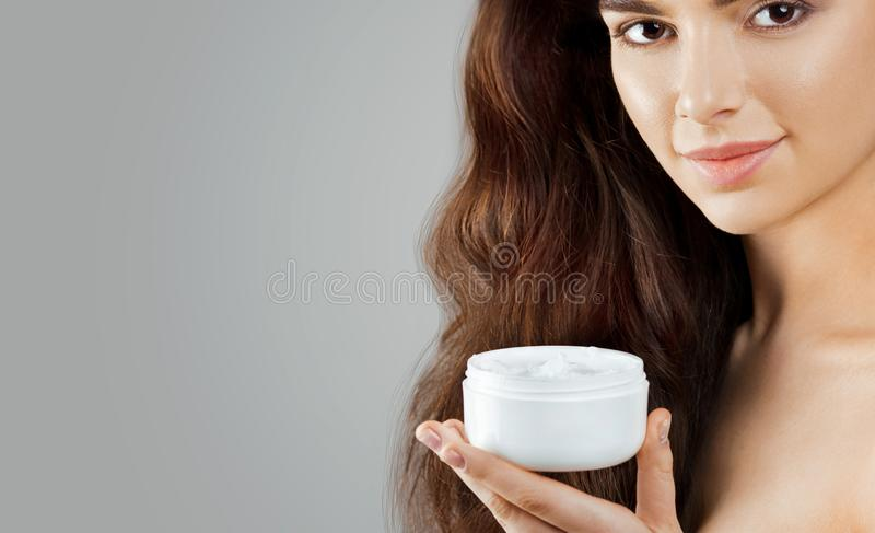Skincare. Beauty Concept. Young pretty woman holding cosmetic cream. Soft skin and naked shoulders,model with light nude make-up, royalty free stock image