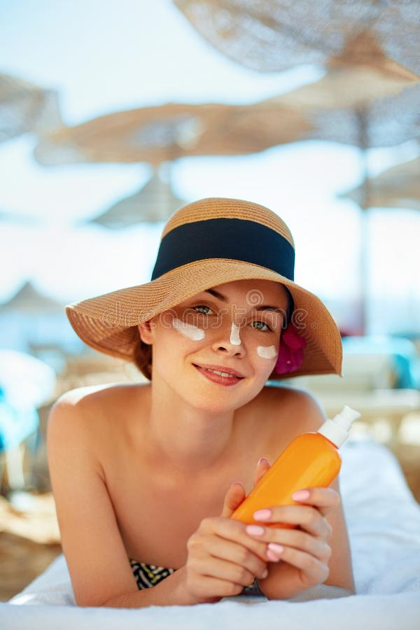Skincare. Beauty Concept. Young pretty woman holding sun cream and applying on her face. stock photo