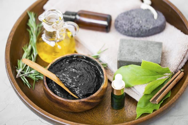 Skincare-Bestandteile mit Holzkohlenmaske, Olivenöl, botanische Kräuterflasche des ätherischen Öls, natürliche Seife, Rosmarinkra stockbild