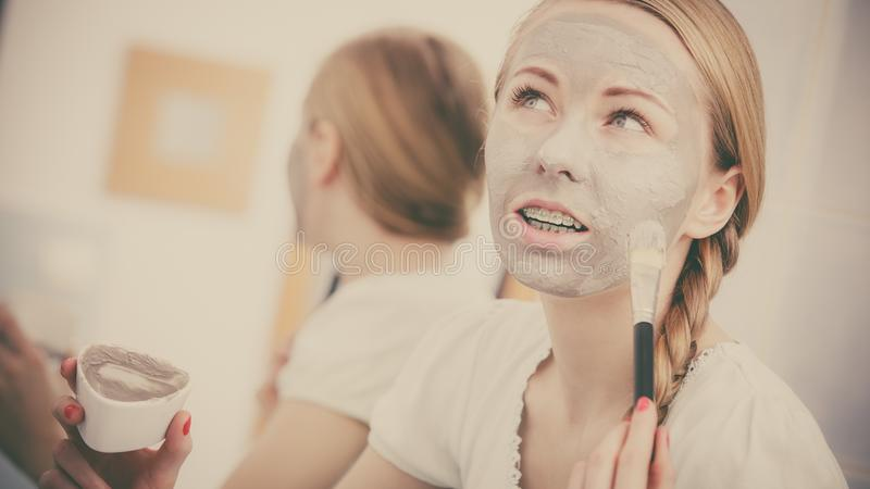 Woman with grey clay mud mask on her face. Skincare. Blonde woman in bathroom with gray clay mud mask on her face. Young lady taking care of skin. Spa beauty stock images