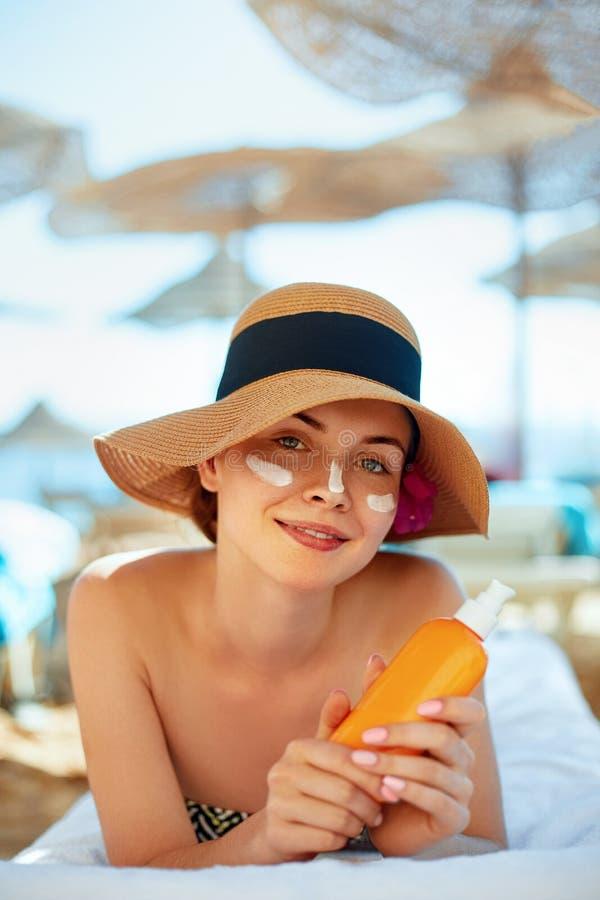 Skincare Conceito da beleza Creme bonito novo do sol da terra arrendada da mulher e aplicação em sua cara foto de stock