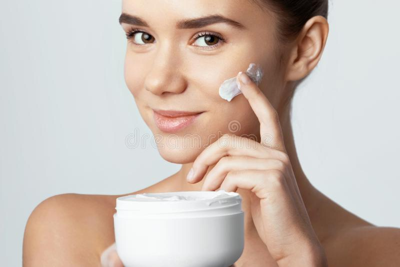 Skincare Conceito da beleza Mulher bonita nova que guarda o creme cosmético imagens de stock royalty free