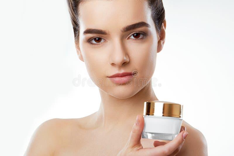 Skincare Conceito da beleza Mulher bonita nova que guarda o creme cosmético cosmetology imagem de stock royalty free