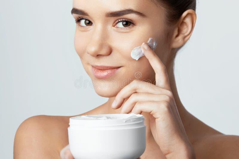Skincare Concetto di bellezza Giovane donna graziosa che tiene crema cosmetica immagini stock libere da diritti