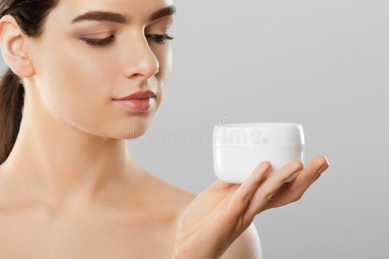 Skincare Concetto di bellezza Giovane donna graziosa che tiene crema cosmetica Pelle molle e spalle nude, modello con trucco nudo immagine stock
