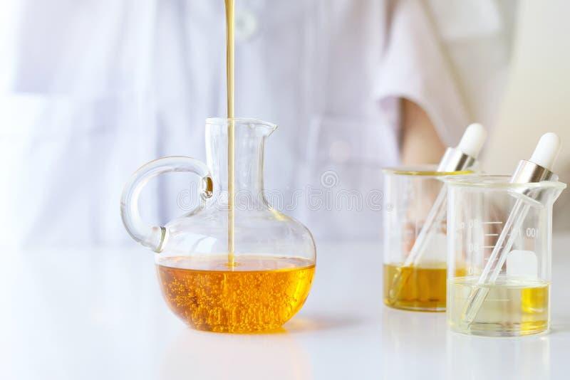 Skincare das ciências dos cosméticos da beleza, da formulação e da mistura com essência erval, cientista que derrama o óleo essen imagem de stock