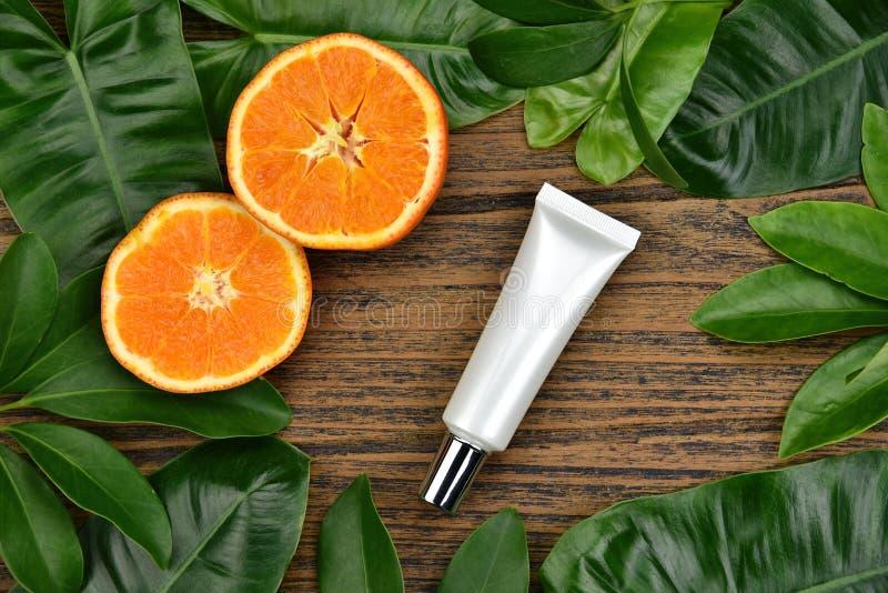 Skincare dei cosmetici con l'estratto della vitamina C, contenitori cosmetici della bottiglia con le fette arancio fresche, etich immagini stock libere da diritti
