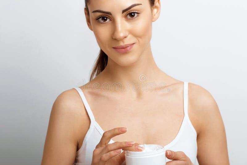 Skincare del fronte Donna con la crema pulita facciale liscia sana della bottiglia della tenuta della pelle Cura del fronte di be fotografia stock