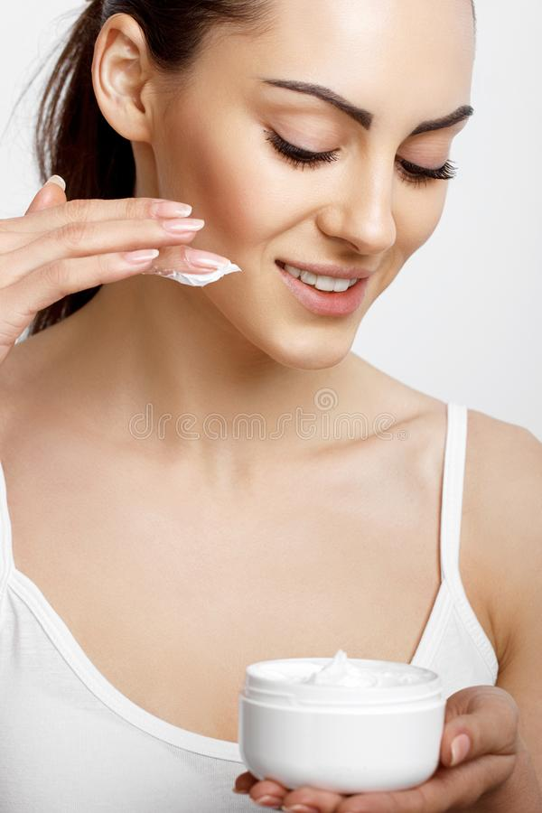 Skincare del fronte Donna con la crema pulita facciale liscia sana della bottiglia della tenuta della pelle Cura del fronte di be immagini stock