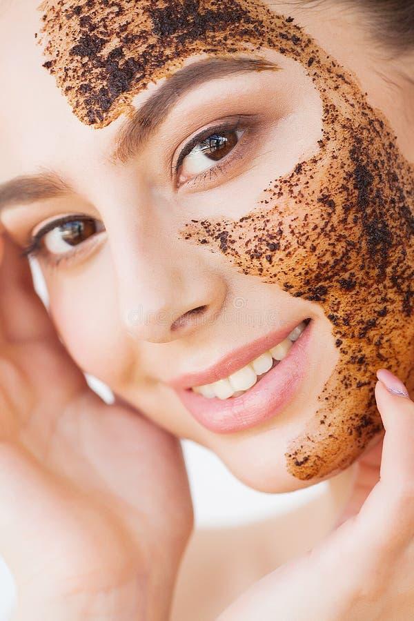 Skincare del fronte La giovane ragazza affascinante fa una maschera nera del carbone sul suo fronte immagini stock libere da diritti