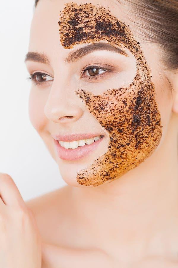 Skincare del fronte La giovane ragazza affascinante fa una maschera nera del carbone sul suo fronte immagine stock libera da diritti