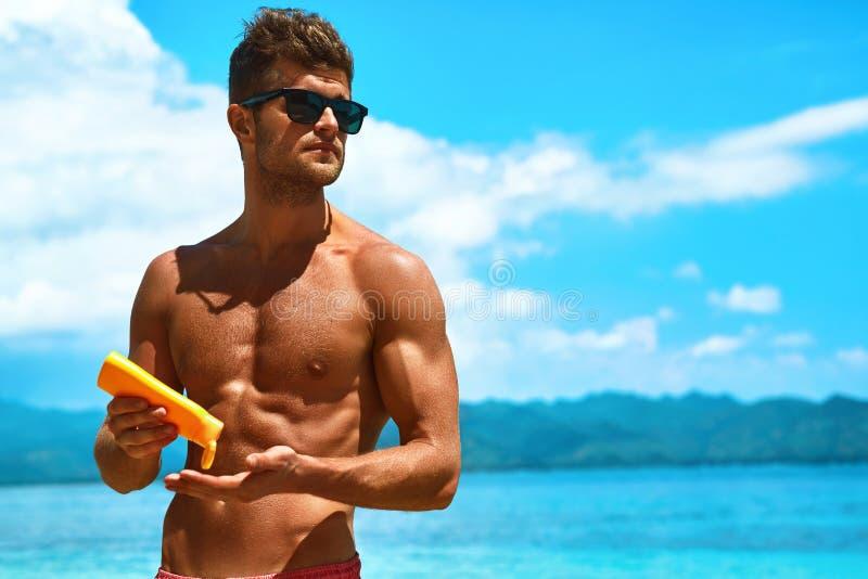 Skincare del verano Hombre que aplica la loción del cuerpo de la protección de la protección solar fotografía de archivo libre de regalías