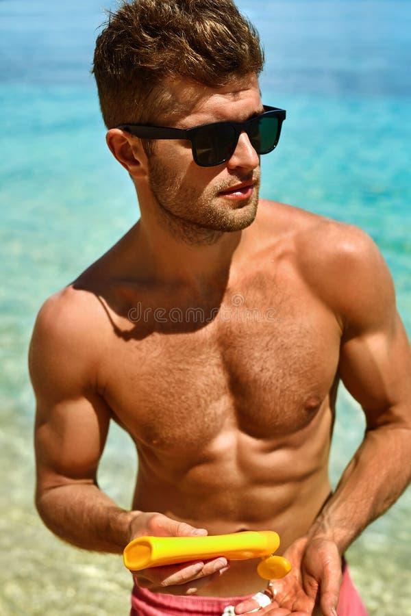 Skincare del verano Hombre que aplica la loción del cuerpo de la protección de la protección solar fotos de archivo