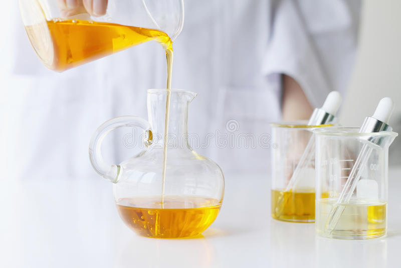 Skincare di formulazione e di mescolanza di scienze dei cosmetici di bellezza, con essenza di erbe, scienziato che versa olio ess immagini stock
