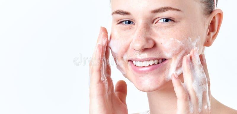 Skincare do adolescente Menina adolescente bonita de sorriso com sardas e olhos azuis usando o limpador de formação de espuma Con fotos de stock royalty free