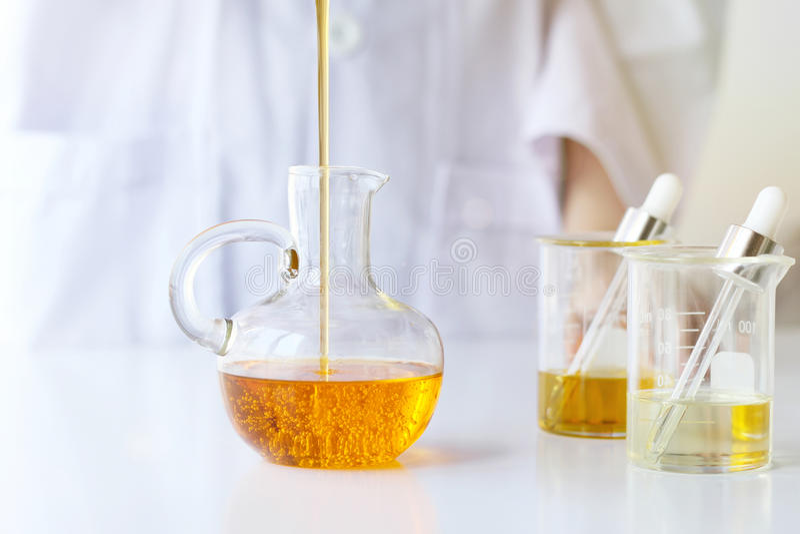 Skincare för vetenskaper för skönhetskönhetsmedel för formulera och blandnings, med växt- extrakt, forskare som häller organisk n fotografering för bildbyråer