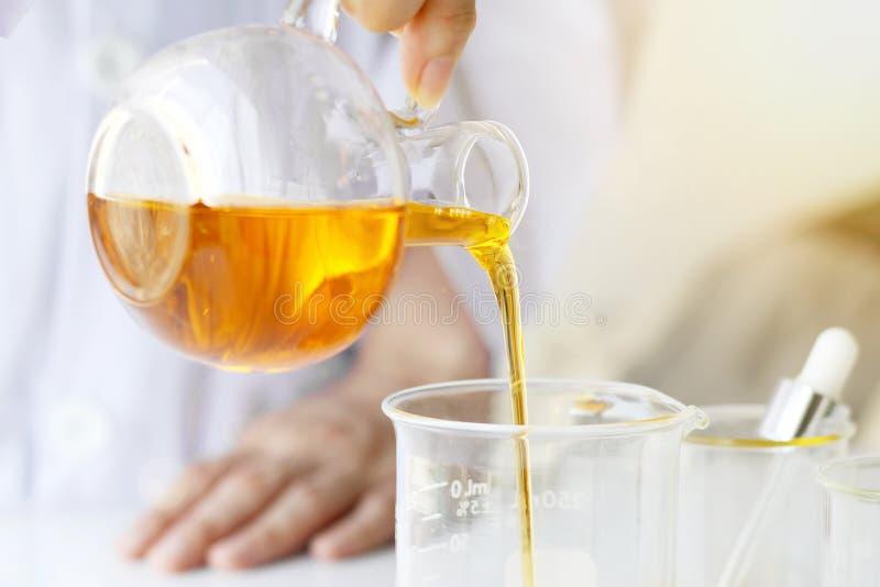 Skincare för vetenskaper för skönhetskönhetsmedel för formulera och blandnings, med växt- extrakt, forskare som häller organisk n arkivbild