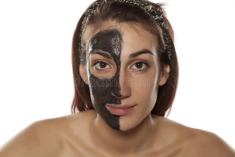 Skincare - face mask. Young woman with mud mask on half of her face royalty free stock photo