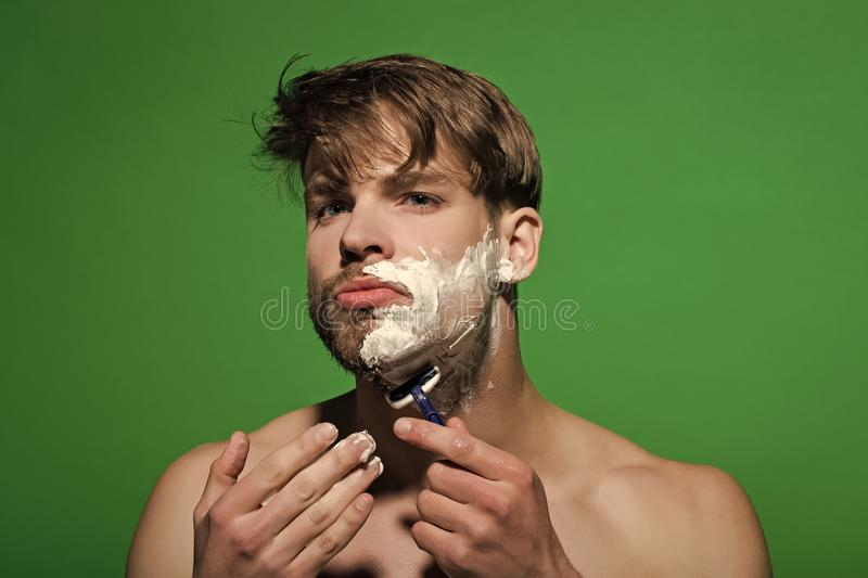 Skincare, health, wellness. Bachelor with shaving cream or foam on face skin. Beauty, grooming, hygiene. Morning routine concept. Man shave beard hair with royalty free stock image