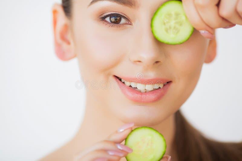 Skincare Jovem mulher bonita com os pepinos nos olhos foto de stock