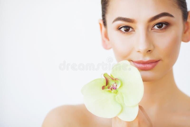 Skincare La belleza de la mujer, hace frente a cuidado de piel y compone, flor de la orquídea de la muchacha fotos de archivo libres de regalías