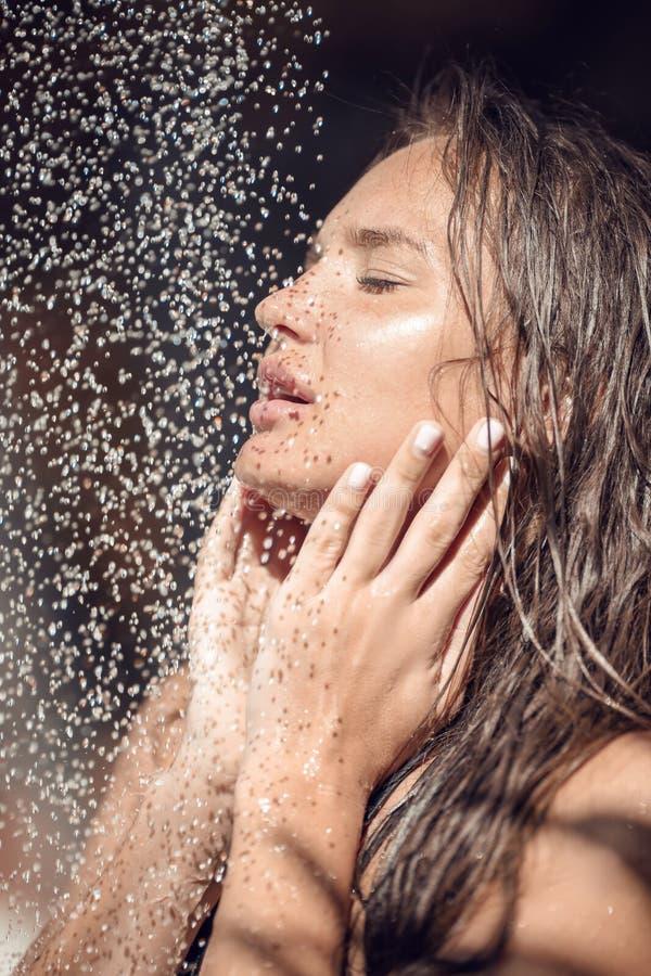 Skincare Muchacha atractiva mojada que goza de la ducha tropical al aire libre en Maldivas Mujer joven que riega afuera por las p foto de archivo libre de regalías
