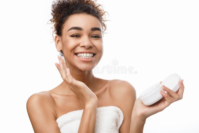 Skincare Mulher que aplica o frasco da terra arrendada do creme de cara com bálsamo imagens de stock