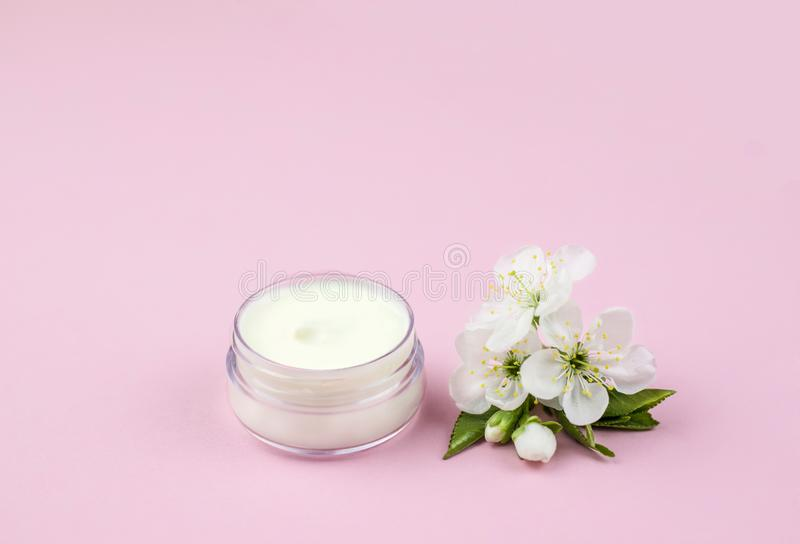 Skincare product for face with spring flowers. Skincare product for face with spring cherry blossom on pink background stock photo