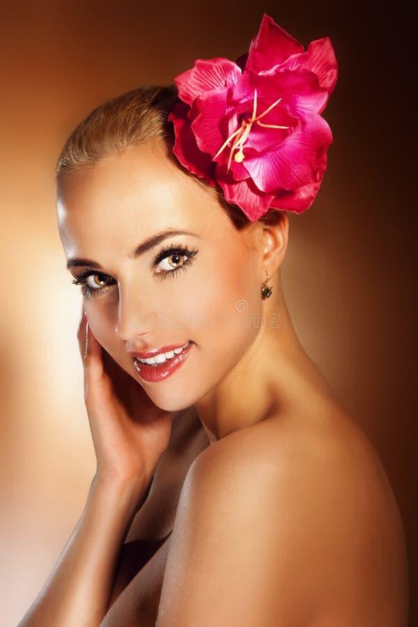 Mooi jong de vrouwengezicht van de close-up met bloem. Het glimlachen van het meisje. stock foto's