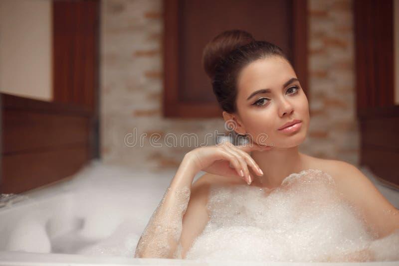 Skincare wellness Jovem mulher que relaxa em termas do banho do Jacuzzi, Br fotografia de stock