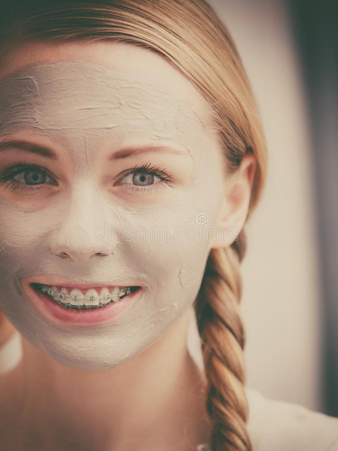 Woman with clay mud mask on her face. Skincare. Young positive woman with grey clay mud mask on her face. Female taking care of skin condition. Spa beauty royalty free stock photos