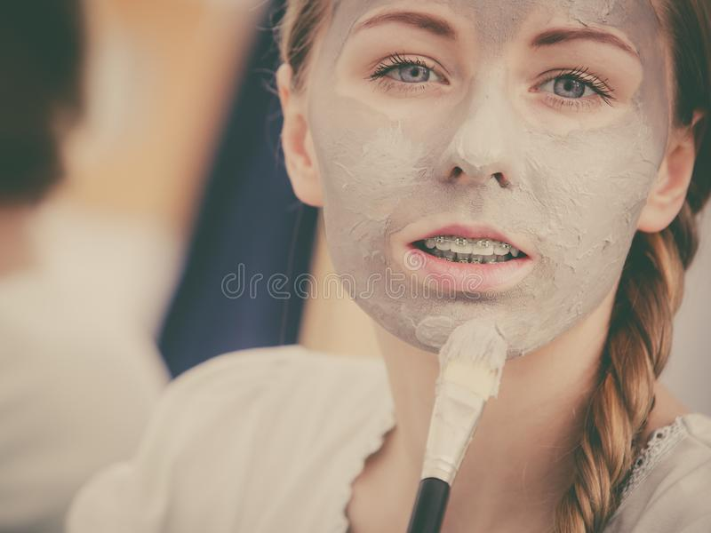 Woman applying with brush clay mud mask to her face. Skincare. Young woman applying with brush grey clay mud mask to her face. Female taking care of skin stock photo