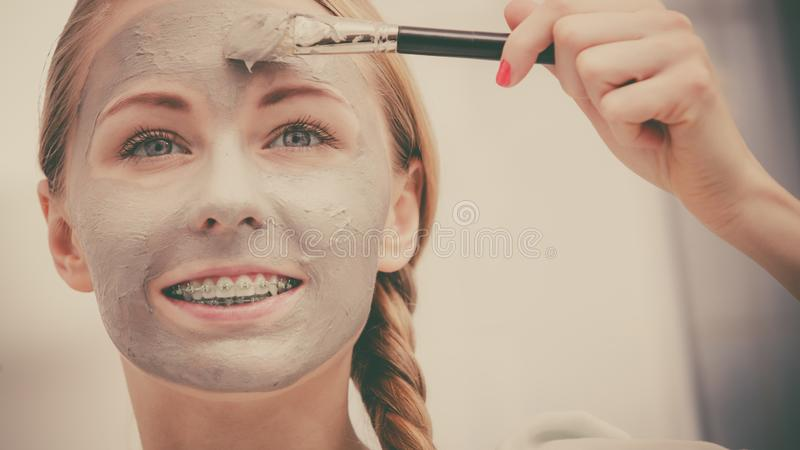 Woman applying with brush clay mud mask to her face. Skincare. Young woman applying with brush grey clay mud mask to her face. Female taking care of skin royalty free stock photo