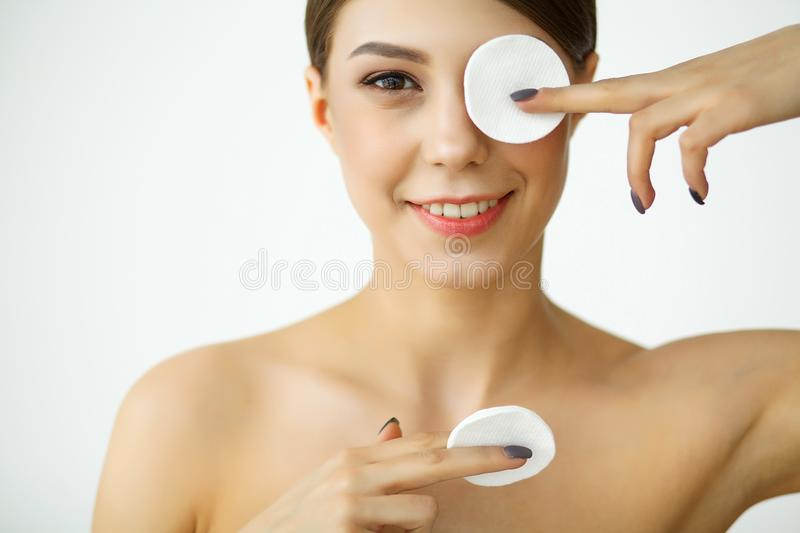 Skincare. Young woman with lotion washing face at bathroom.  stock photo