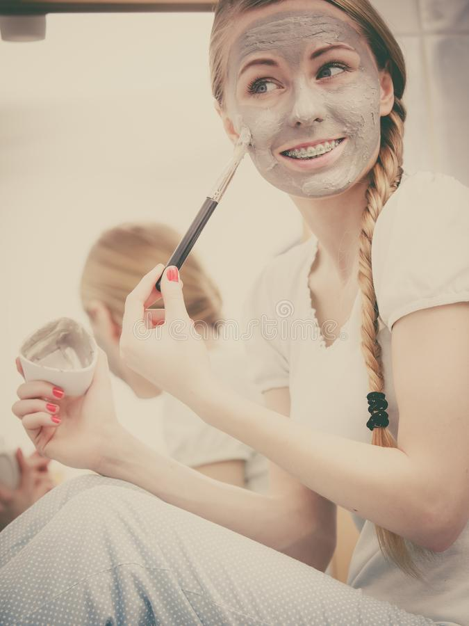 Woman applying with brush clay mud mask to her face. Skincare. Young woman wearing nightwear sitting on sink in bathroom, applying with brush gray clay mud mask royalty free stock images