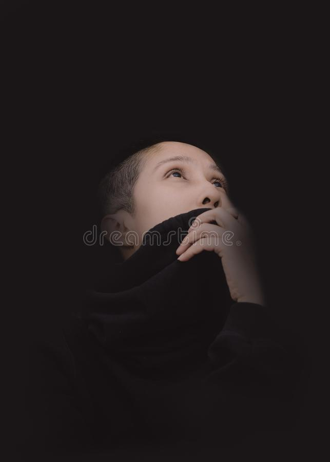 The skinhead woman put her hand closed her mounth on the black s stock photography