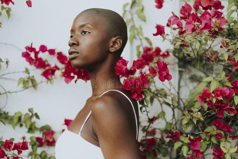 Skinheadkvinna som omges av röda blommor arkivfoton