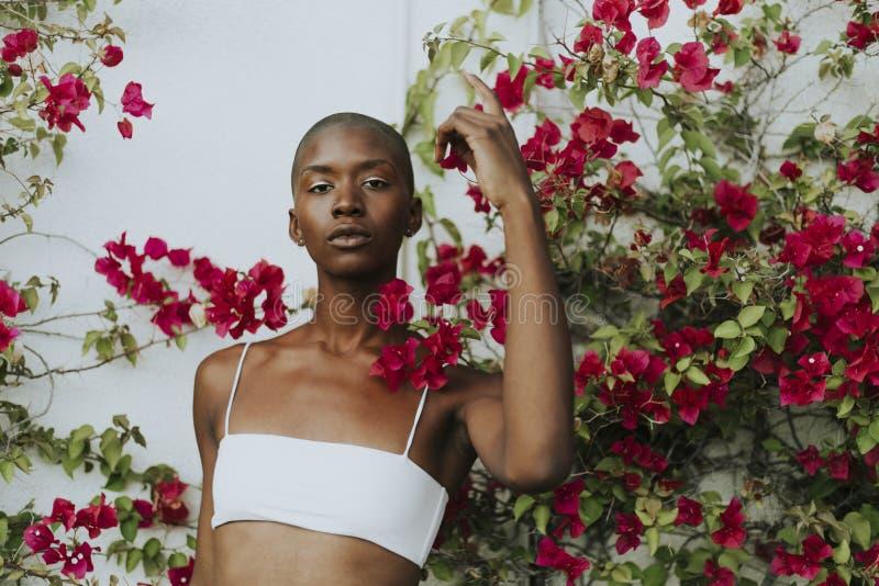 Skinheadkvinna som omges av röda blommor fotografering för bildbyråer