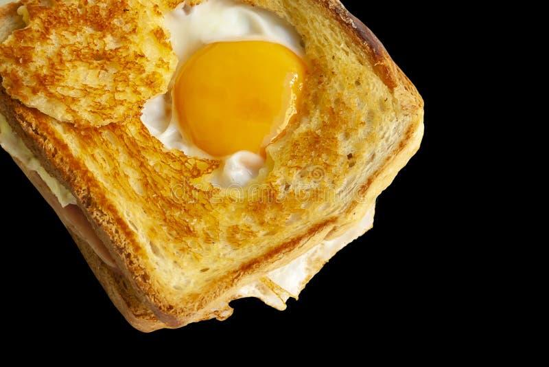 Skinka och ostsmörgås med det stekte ägget som isoleras på svart bakgrund royaltyfria foton