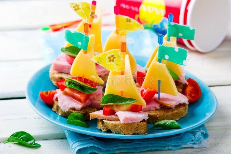 Skinka och ostsmörgåsar i form av skepp royaltyfri bild