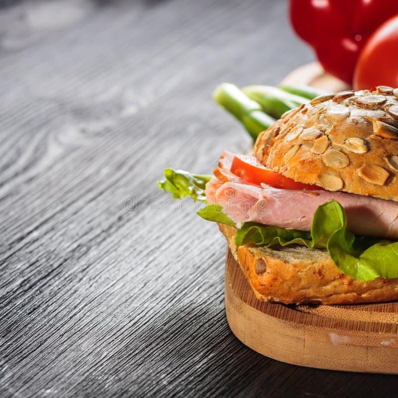 Skinksmörgås med grönsallat royaltyfri bild