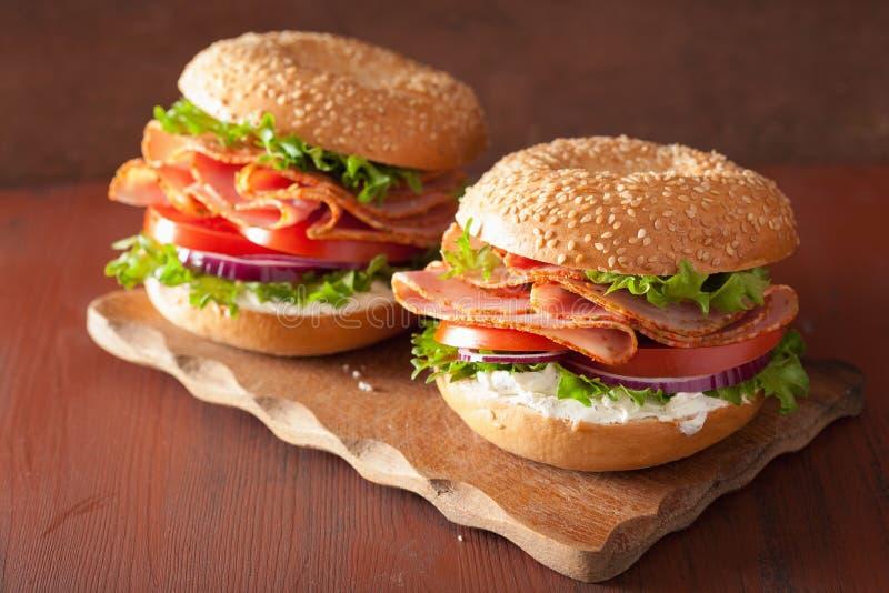 Skinksmörgås på bageln med gräddosttomatlöken royaltyfri foto