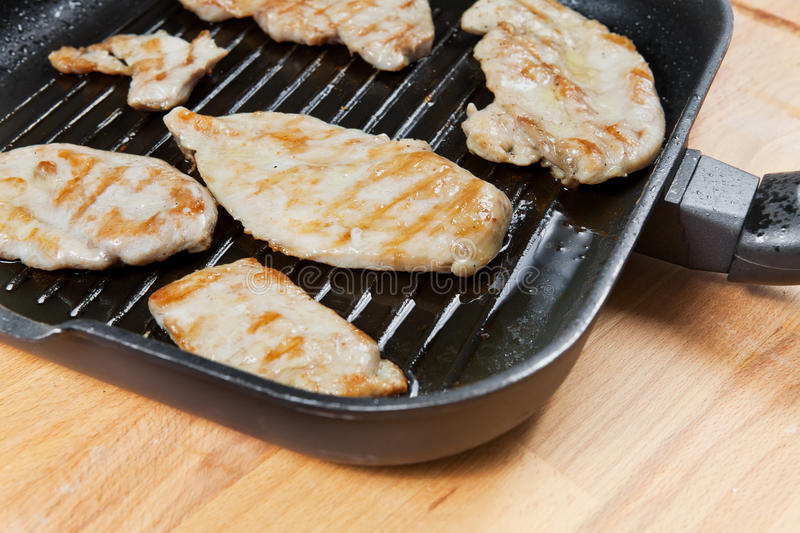 Skinless chicken breast in a pan. Skinless chicken breast fried in a pan with vegetable and olive oil, on a wooden board stock photography