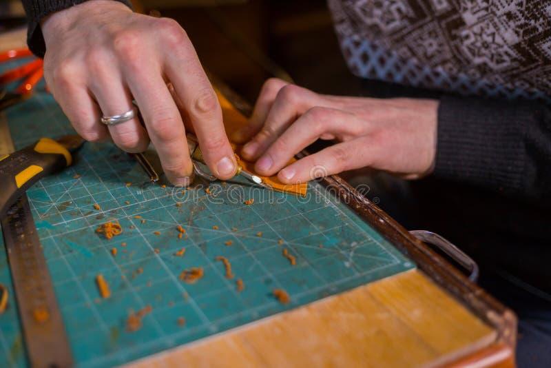 Skinner travaillant avec la ceinture en cuir images stock