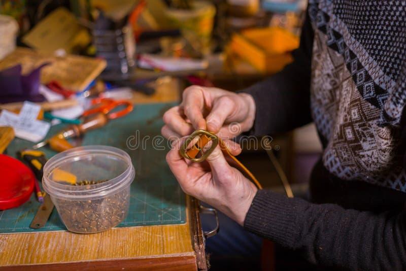 Skinner travaillant avec la ceinture en cuir photos stock