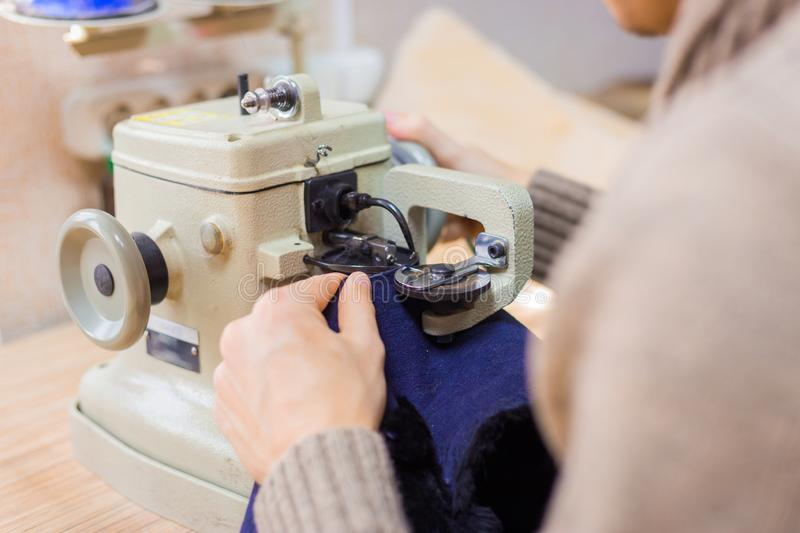 Skinner using sewing machine for stitching fur skin at atelier. Professional male skinner, furrier using special sewing machine for stitching fur skin at atelier stock image