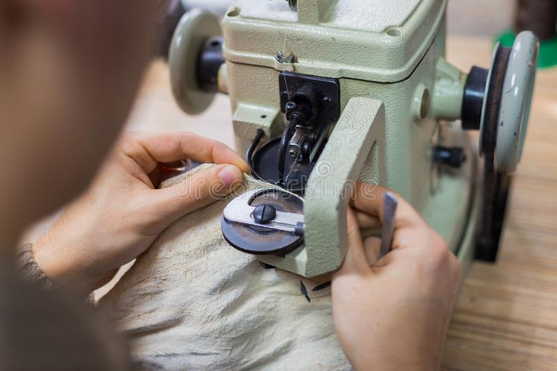 Skinner using sewing machine for stitching fur skin at atelier. Professional male skinner, furrier using special sewing machine for stitching fur skin at atelier royalty free stock image
