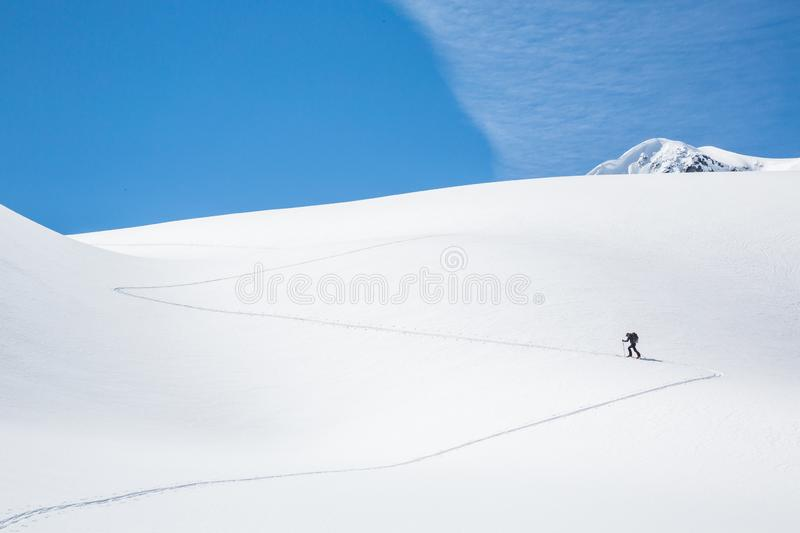 Skinning up the Asulkan Glacier in Glacier National Park, British Columbia. A man hikes on skis to access the Seven Steps to stock photography