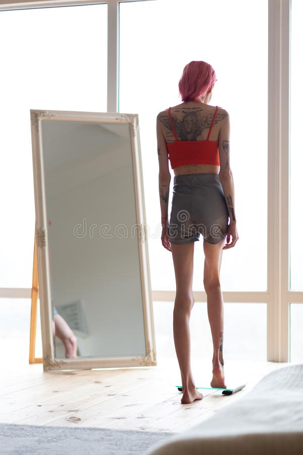 Skinny anorexic woman standing on weight scales near the mirror royalty free stock photography