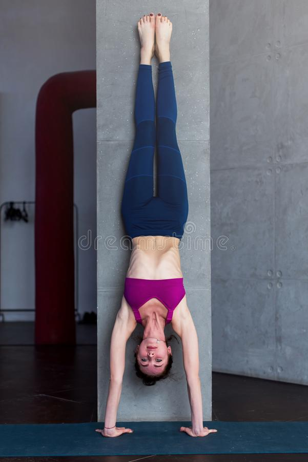 Skinny barefoot woman in sportswear doing handstand against the wall indoors.  stock photos